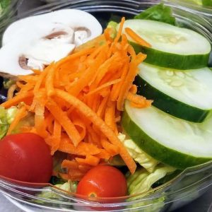 a bowl of salad with carrots shavings, cucumber slices, mushroom slices and cherry tomatoes
